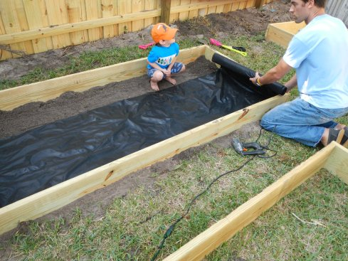 installing weed barrier in raised bed garden